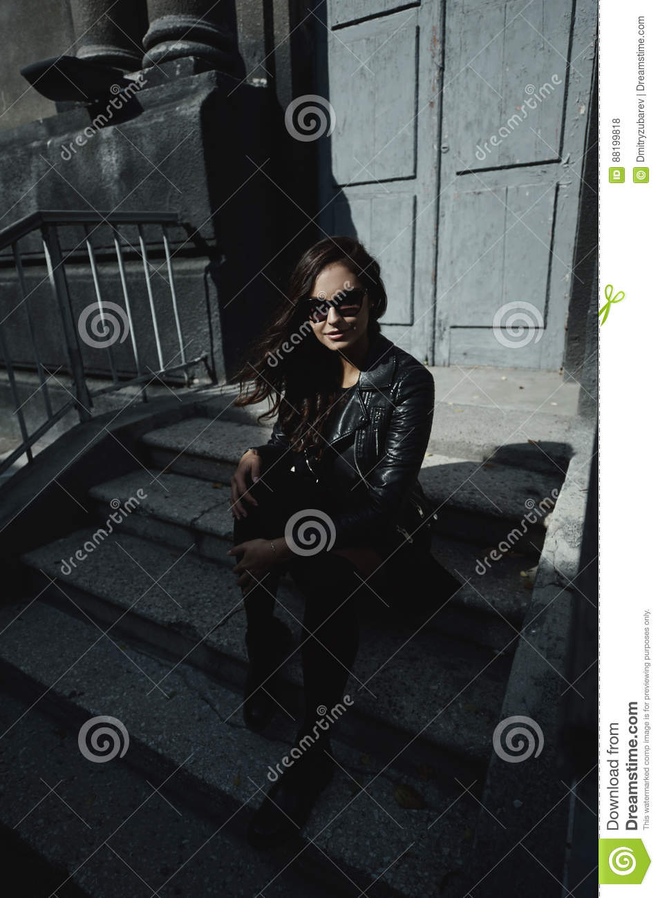 Eastern beautiful woman wearing biker jacket poses in backyard of vintage apartment house
