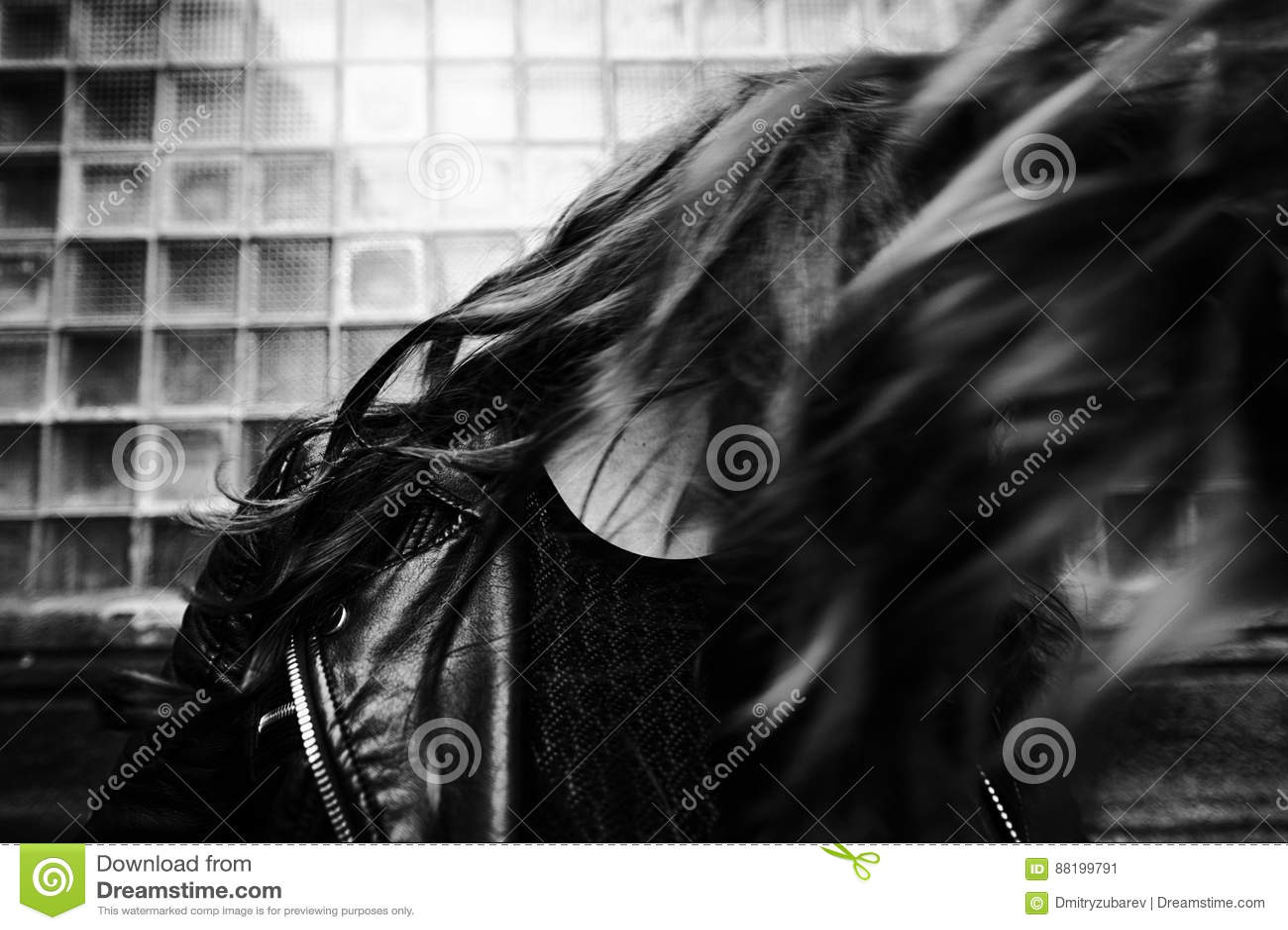 Eastern beautiful woman wearing biker jacket poses in backyard of vintage apartment house