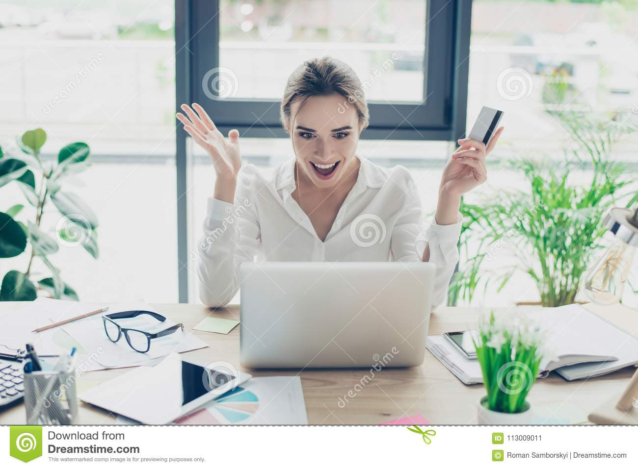 f0609a075b Excited business lady in formal wear is doing online shopping in internet.  She is relaxing and buying goods easily, nice wrk place, windows behind  her, ...