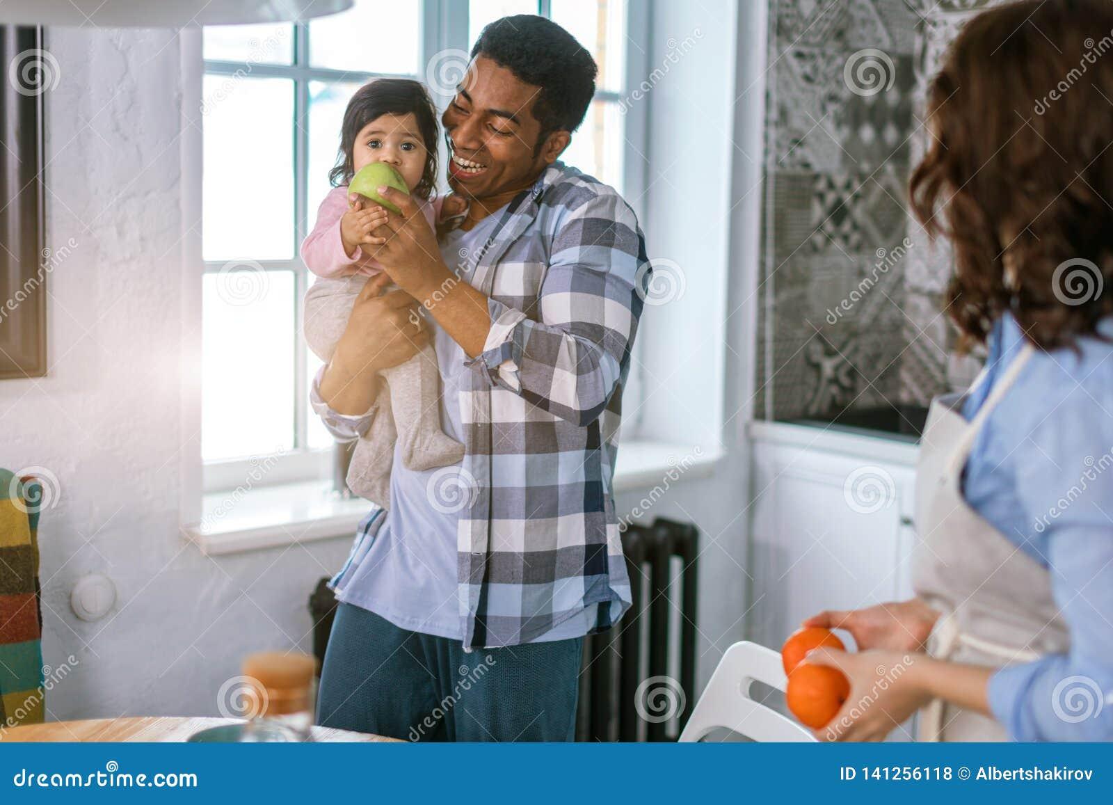 Eathing frukt för liten flicka, medan vara håll i hennes pappas armar