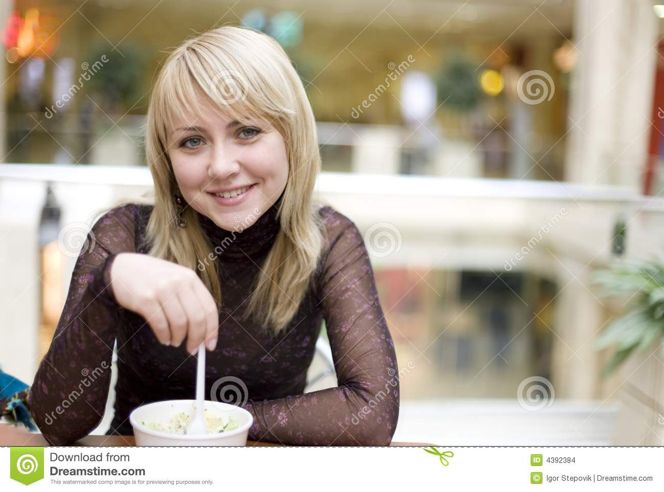 Eating blond girl with spoon in restaurant