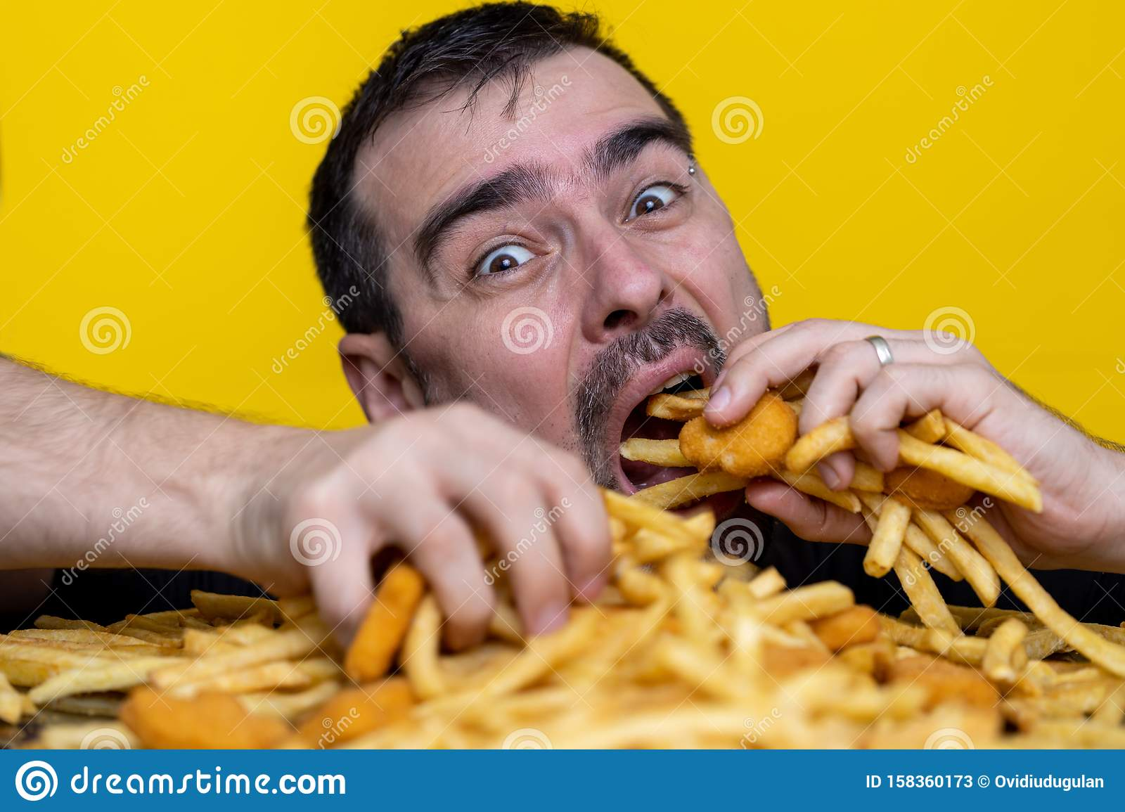 Eating junk food nutrition and dietary health problem concept. Young man eating with two hands a huge amount of unhealthy fast