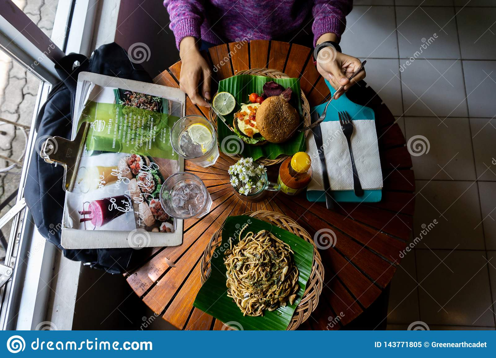 Eating an organic healthy food on the wooden round table. There are spaghetti with black pepper serving on the green banana leaf
