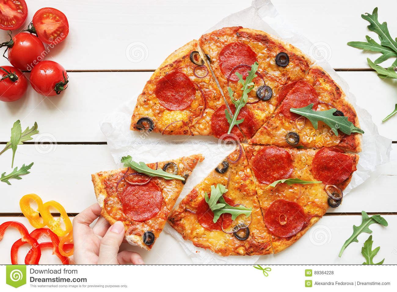 Eating pizza, top view. Hand taking slice of hot delisious pizza on the white wooden table