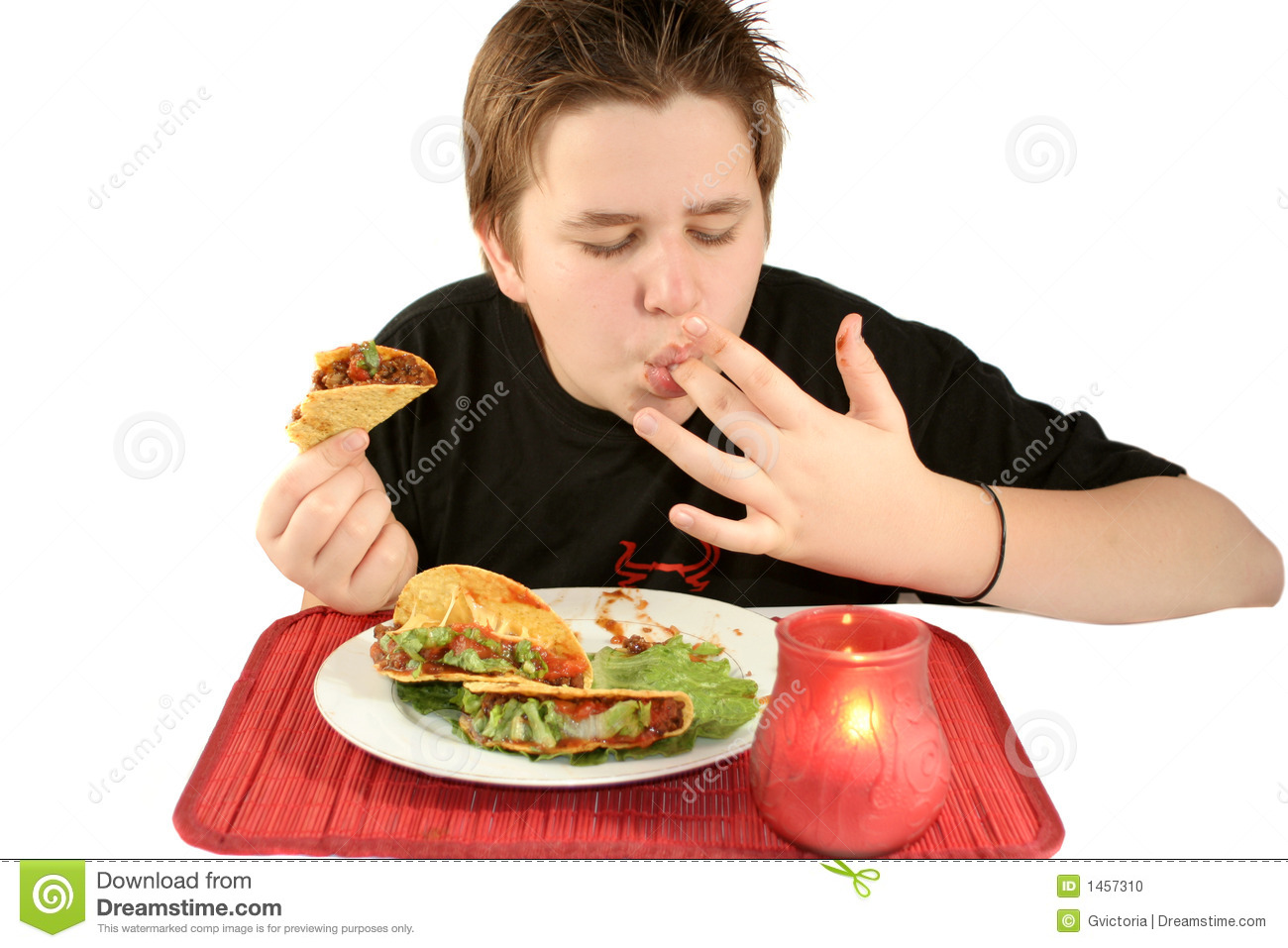 Boy licks his fingers while enjoying his taco dinner at a Mexican ...