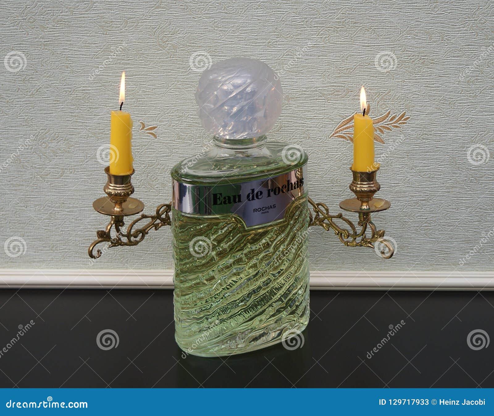 Eau de Rochas, fragrância para senhoras, grande garrafa de perfume na frente dos candelabros de um piano com velas de brilho