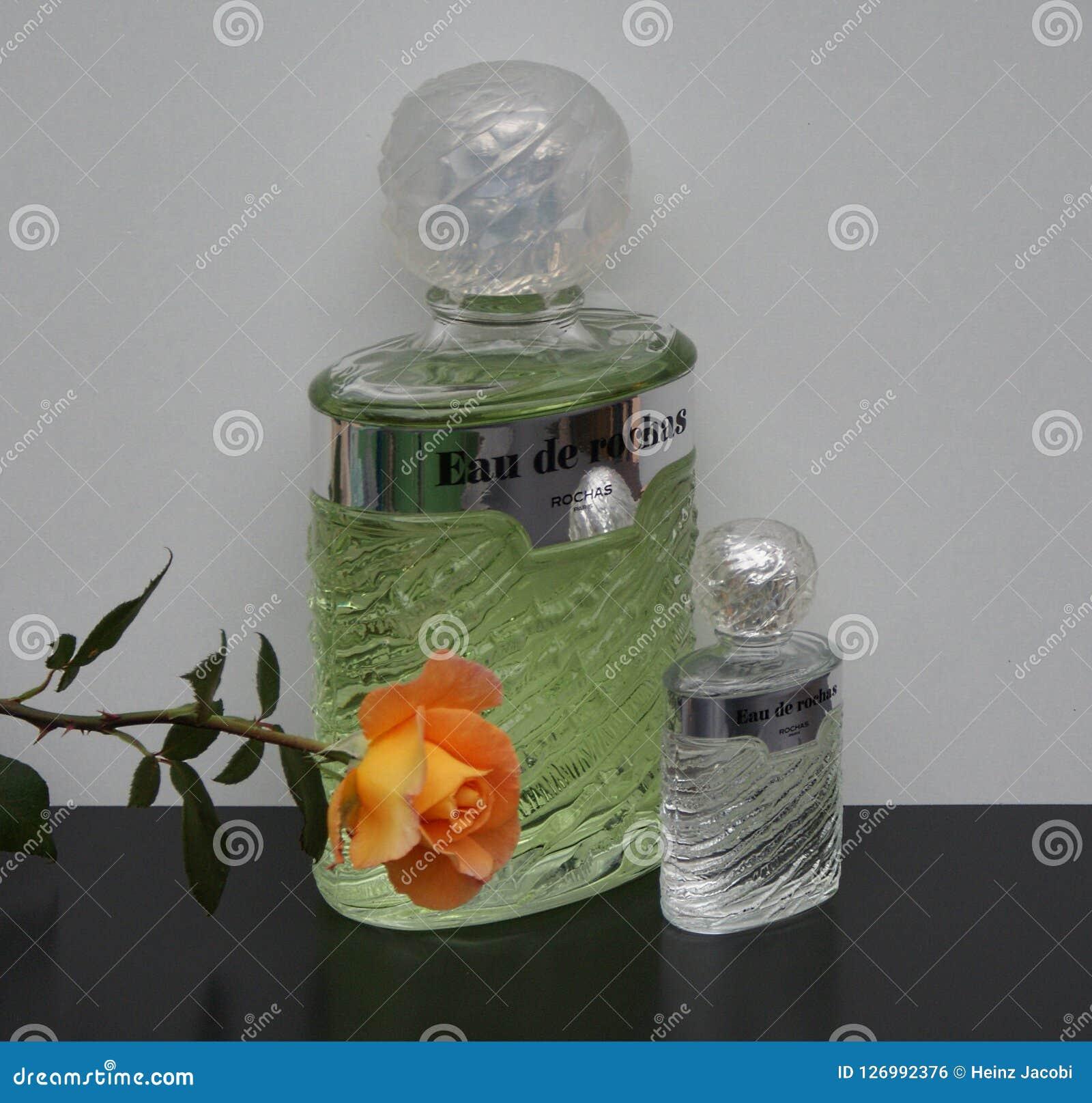 Eau de Rochas, fragranza per le signore, grande bottiglia di profumo accanto ad una bottiglia di profumo commerciale decorata con