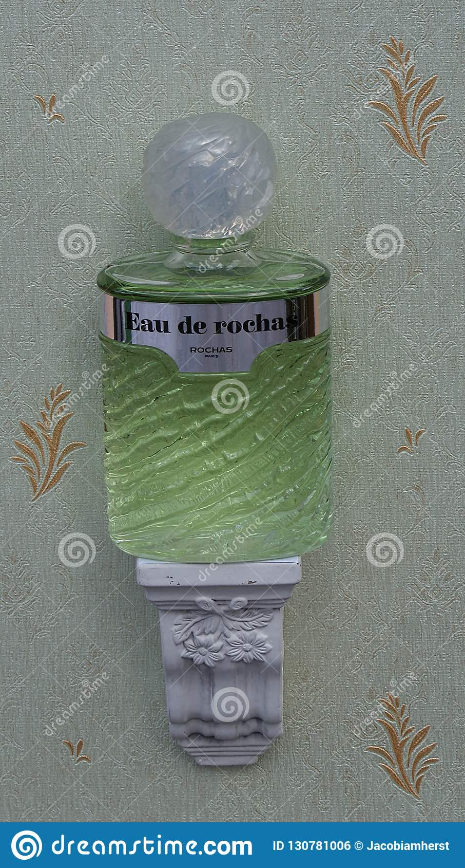 Eau De Rochas, woń dla dam, wielka pachnidło butelka na antyk ściany konsoli z ornamentem