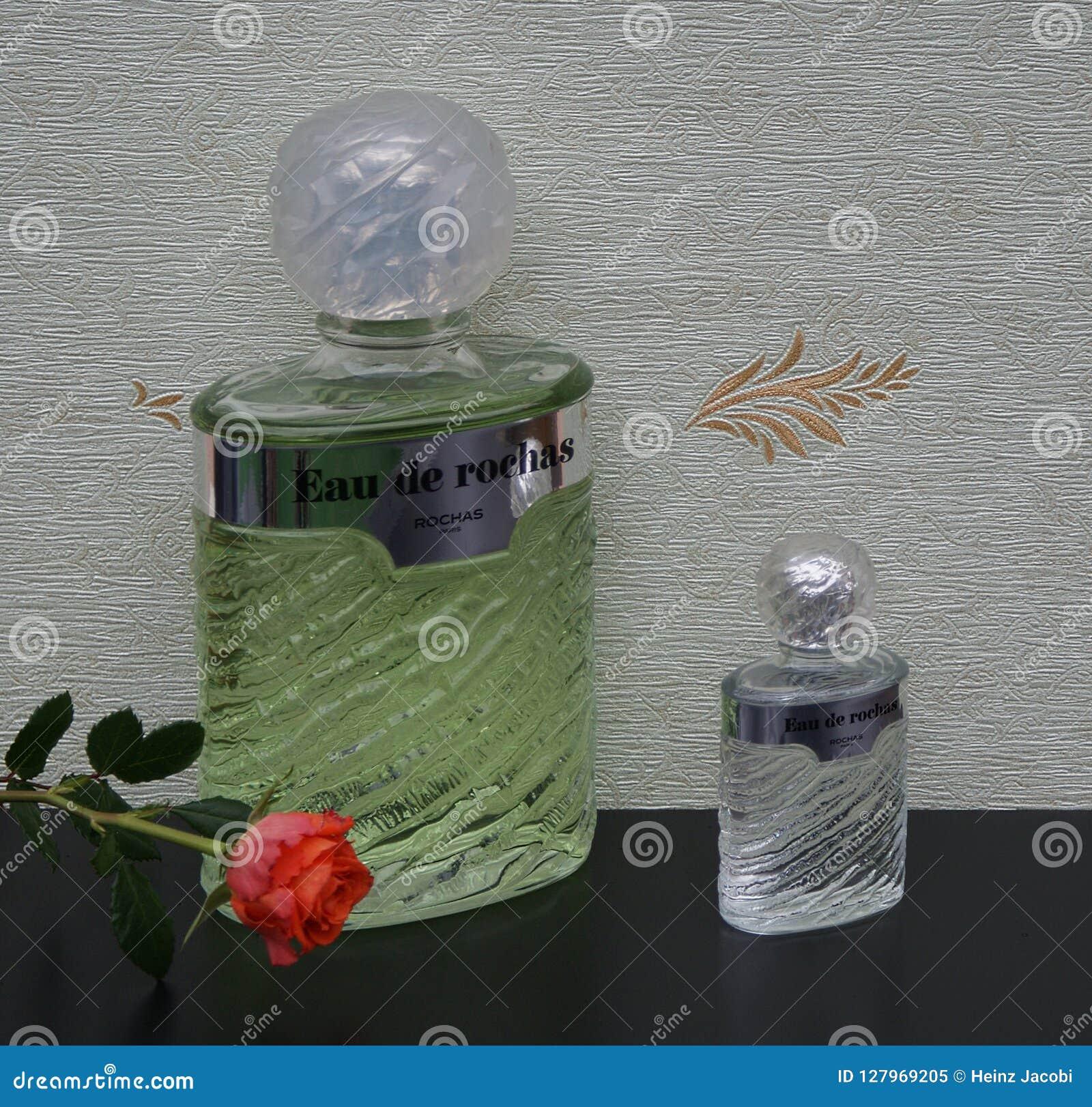 Eau De Rochas, woń dla dam, wielka pachnidło butelka obok handlowej pachnidło butelki przed atłasowym wallcovering