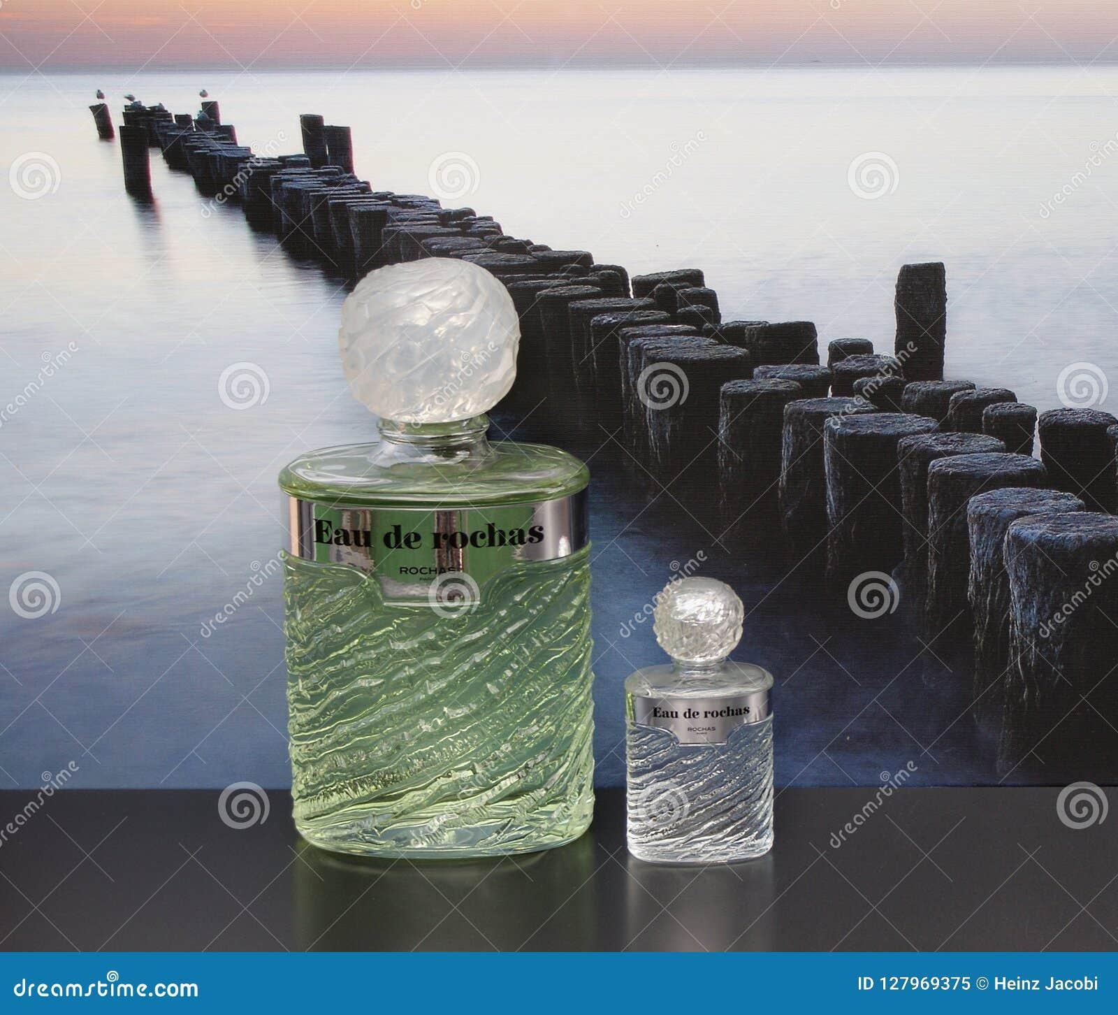 Eau De Rochas, woń dla dam, wielka pachnidło butelka obok handlowej pachnidło butelki przed obrazkiem groyne
