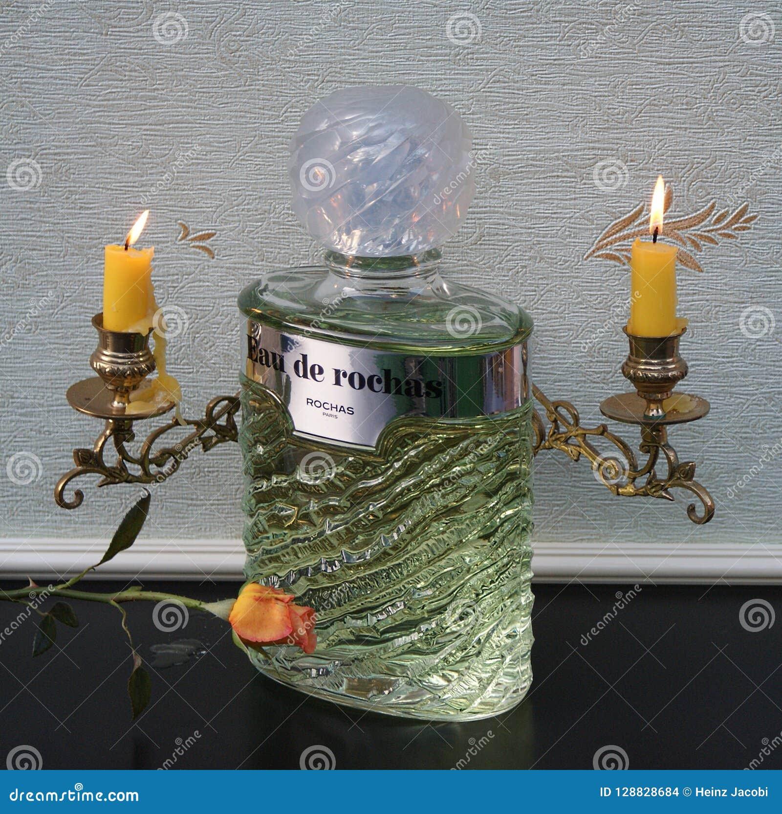 Eau De Rochas woń dla damy pachnidła dużej butelki przed fortepianowi kandelabry z olśniewającymi świeczkami dekorował z różą