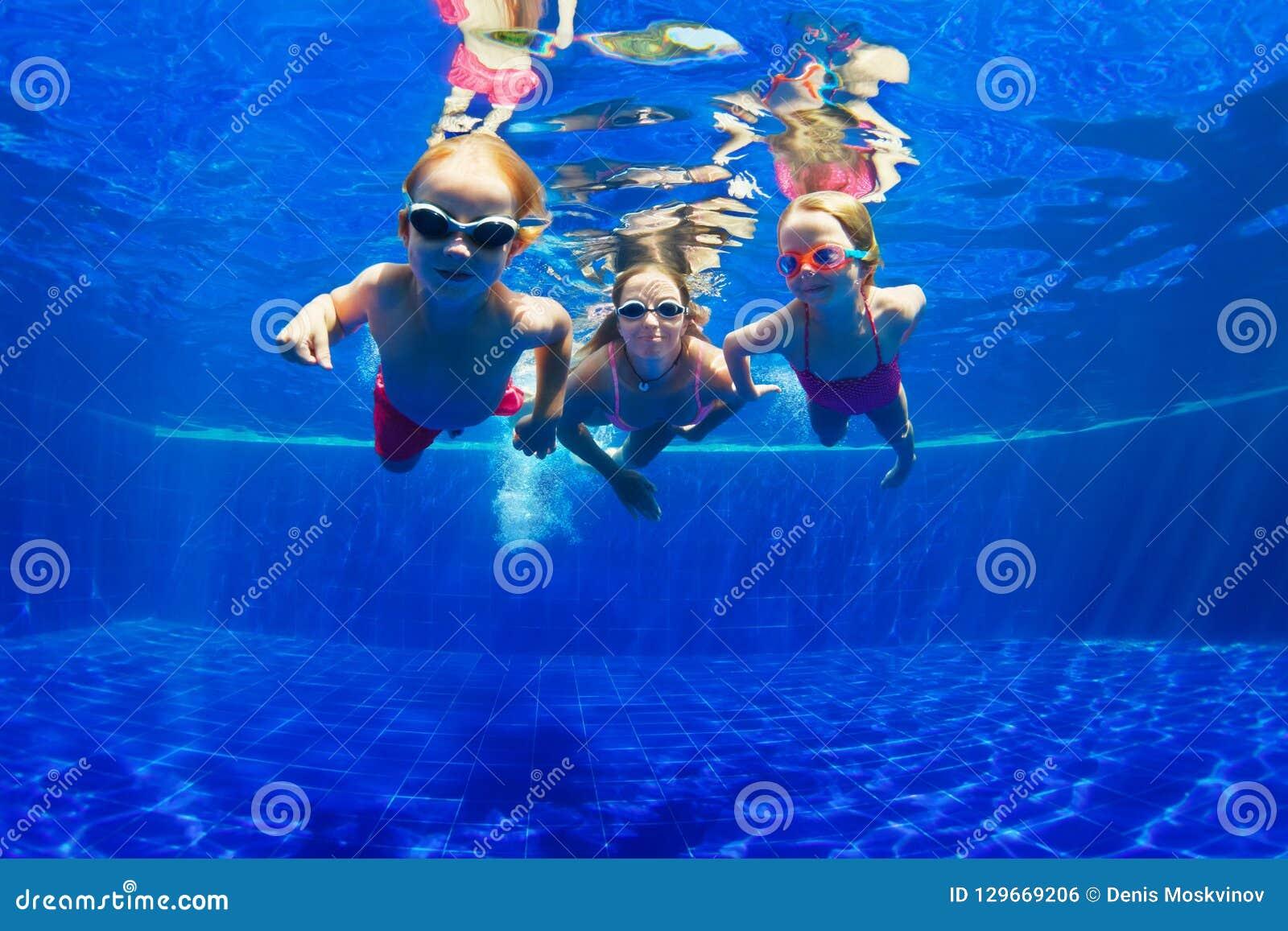 Eau du fond heureuse de piqué de famille dans la piscine