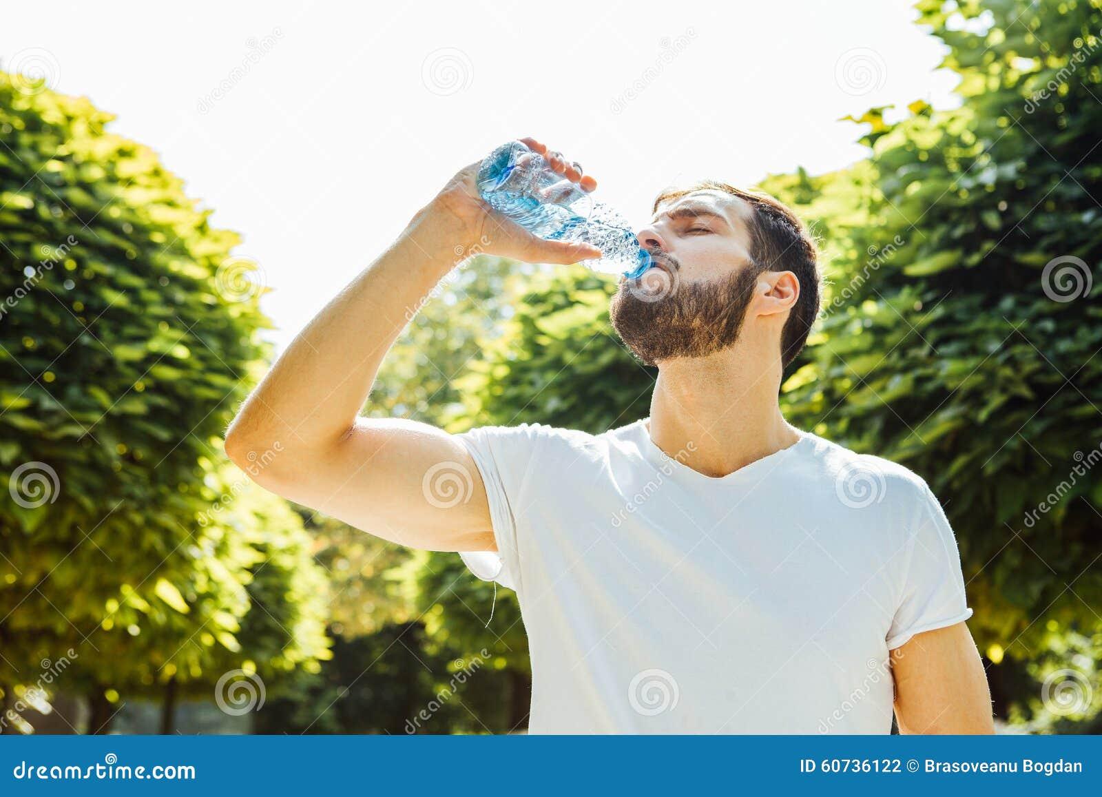 Eau potable d homme adulte d une bouteille dehors
