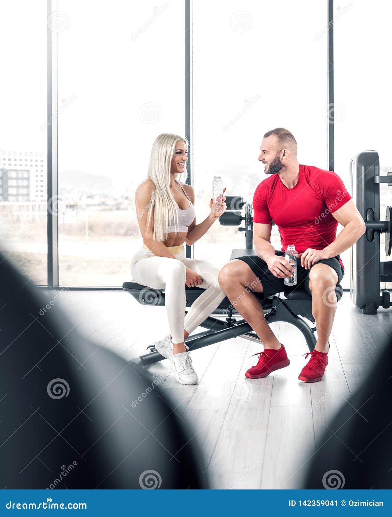 Eau potable de couples de forme physique dans le gymnase