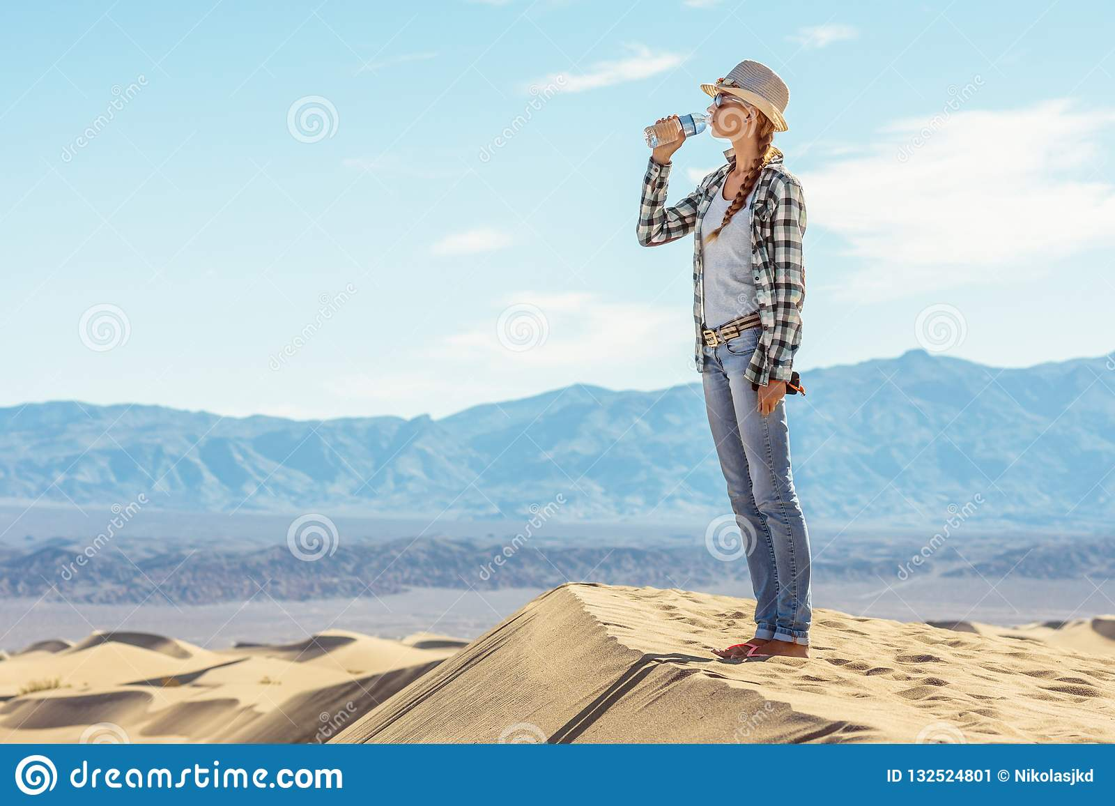 Eau potable de femme dans le désert La fille active éteint la soif dans Death Valley, la Californie, Etats-Unis