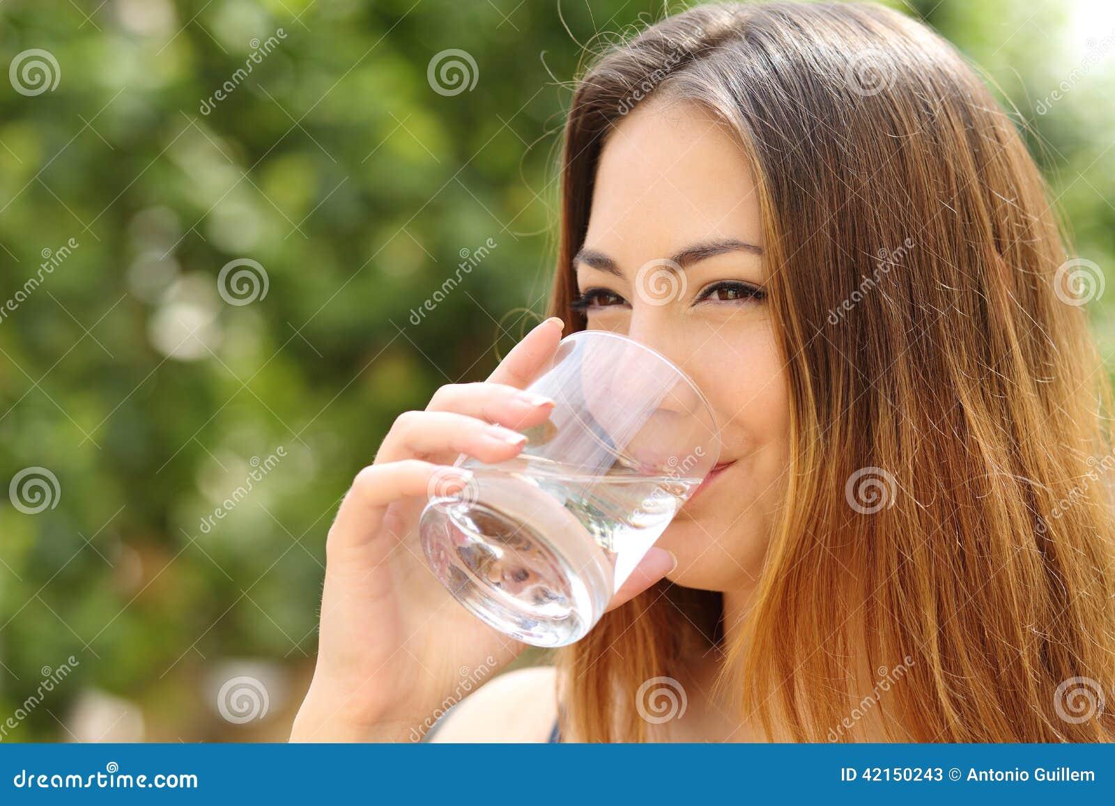 Eau potable de femme heureuse d un verre extérieur