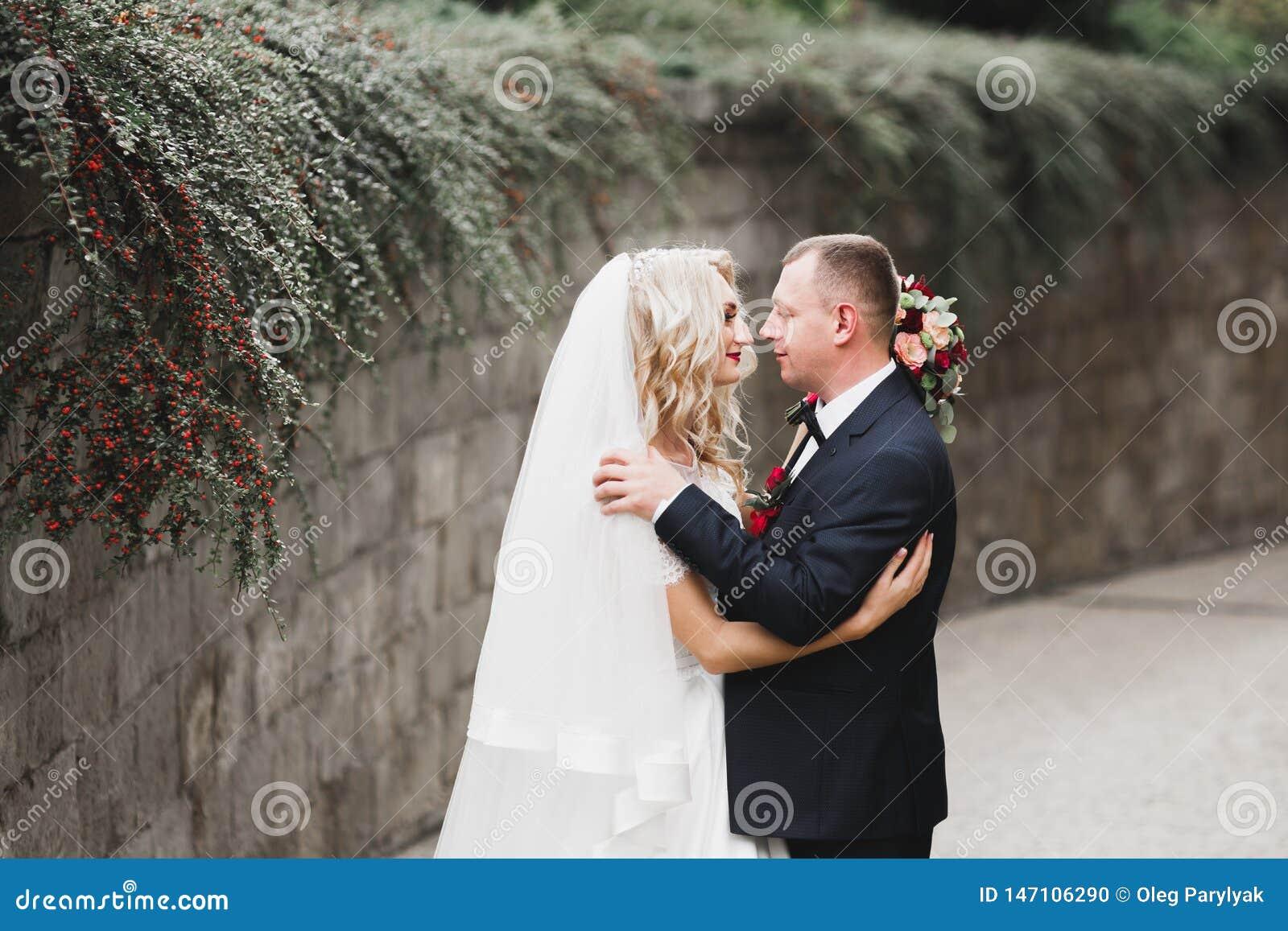 Eben verheiratetes Paar, das in Park w?hrend H?ndchenhalten l?uft und springt
