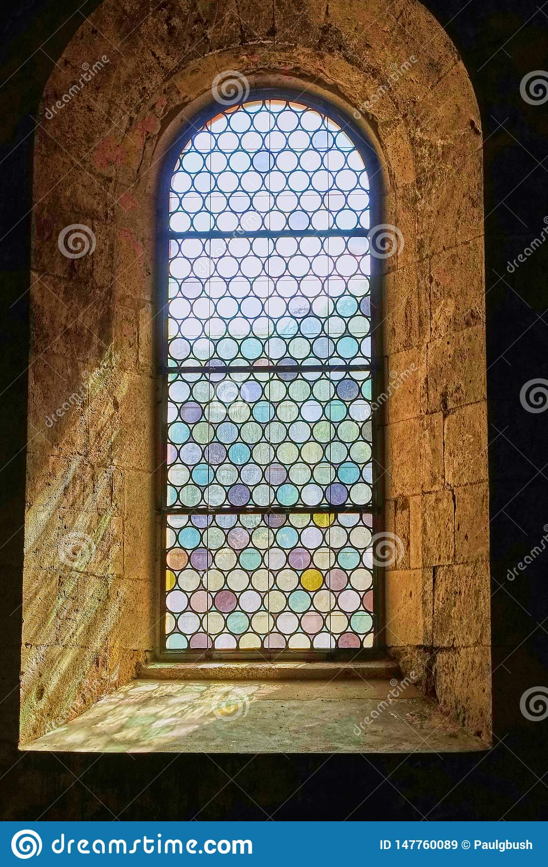 Pretty leaded stained glass window set in thick stone walls