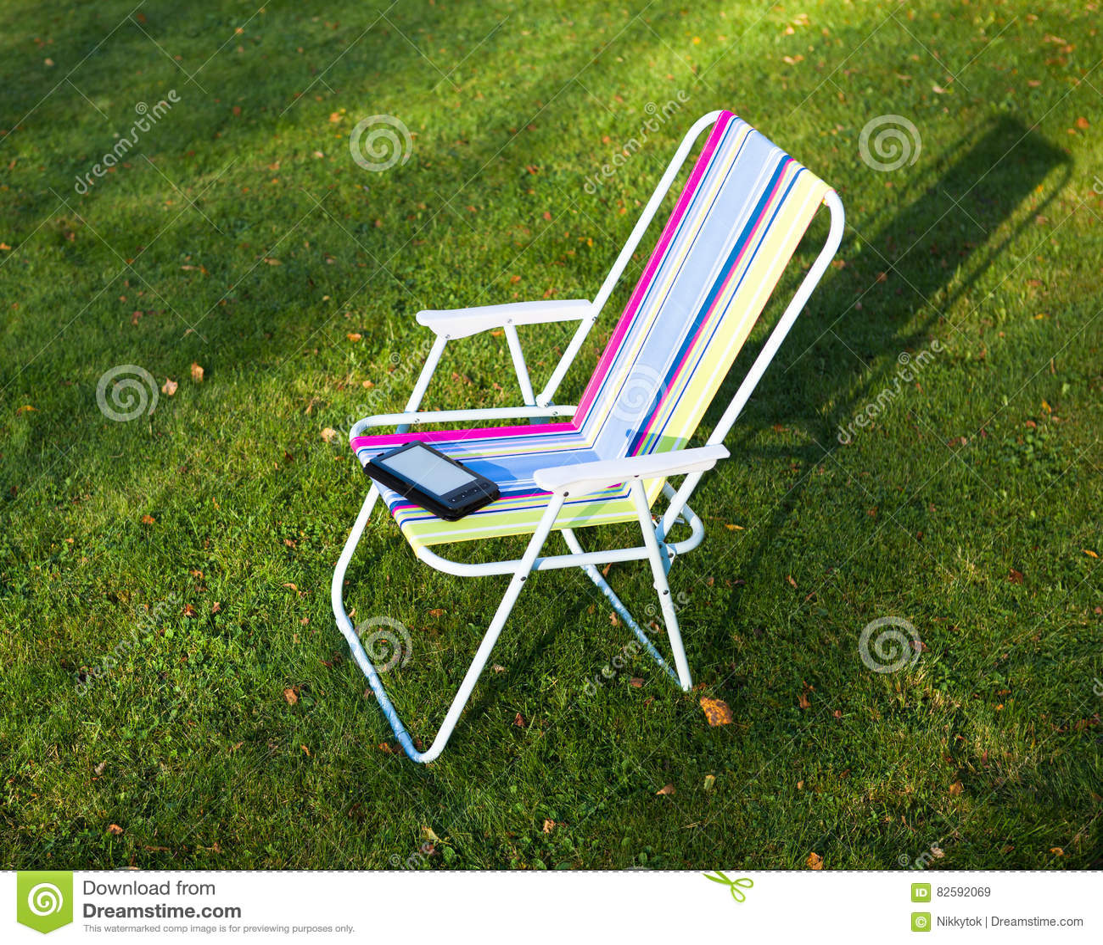 EBook-Leser auf dem Stuhl, Grashintergrund