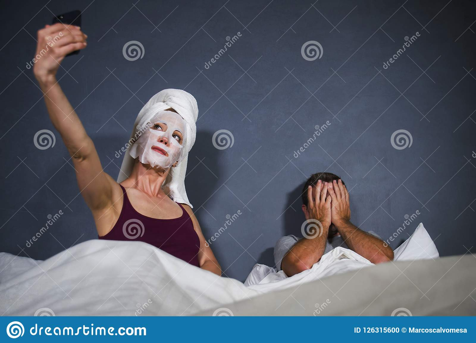 Eccentric housewife with makeup facial mask and towel taking selfie in bed and husband with desperate face expression in weird man