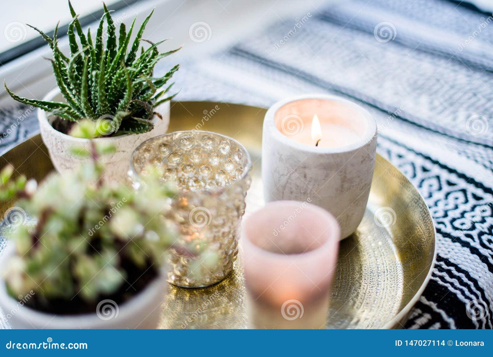 Echt flat binnenlands decor, aromatische kaarsen en installaties op uitstekend dienblad met hoofdkussens en deken op witte venste