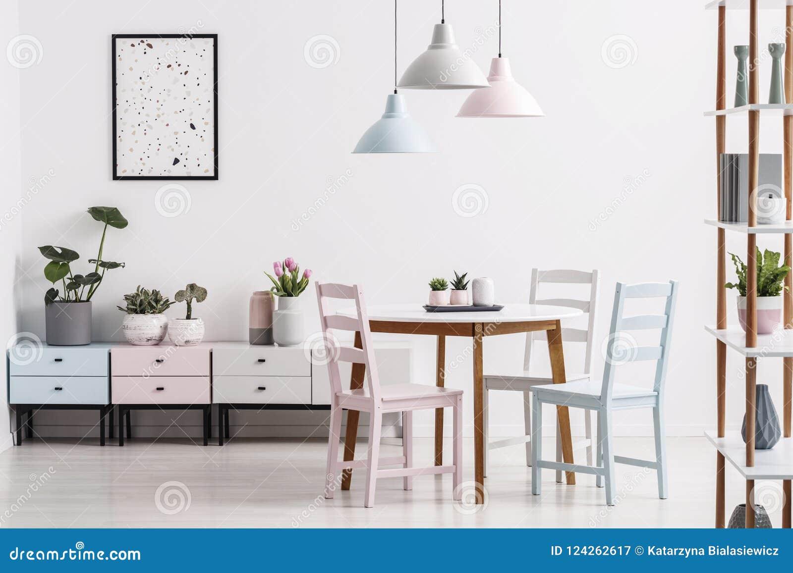 Echte foto van een binnenland van de pastelkleureetkamer met een lijst, stoelen