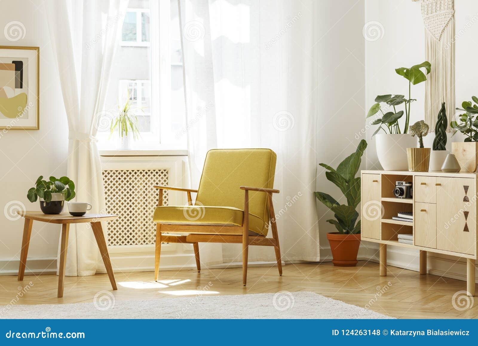Echte foto van een retro leunstoel, een koffietafel en een kabinet in een Li