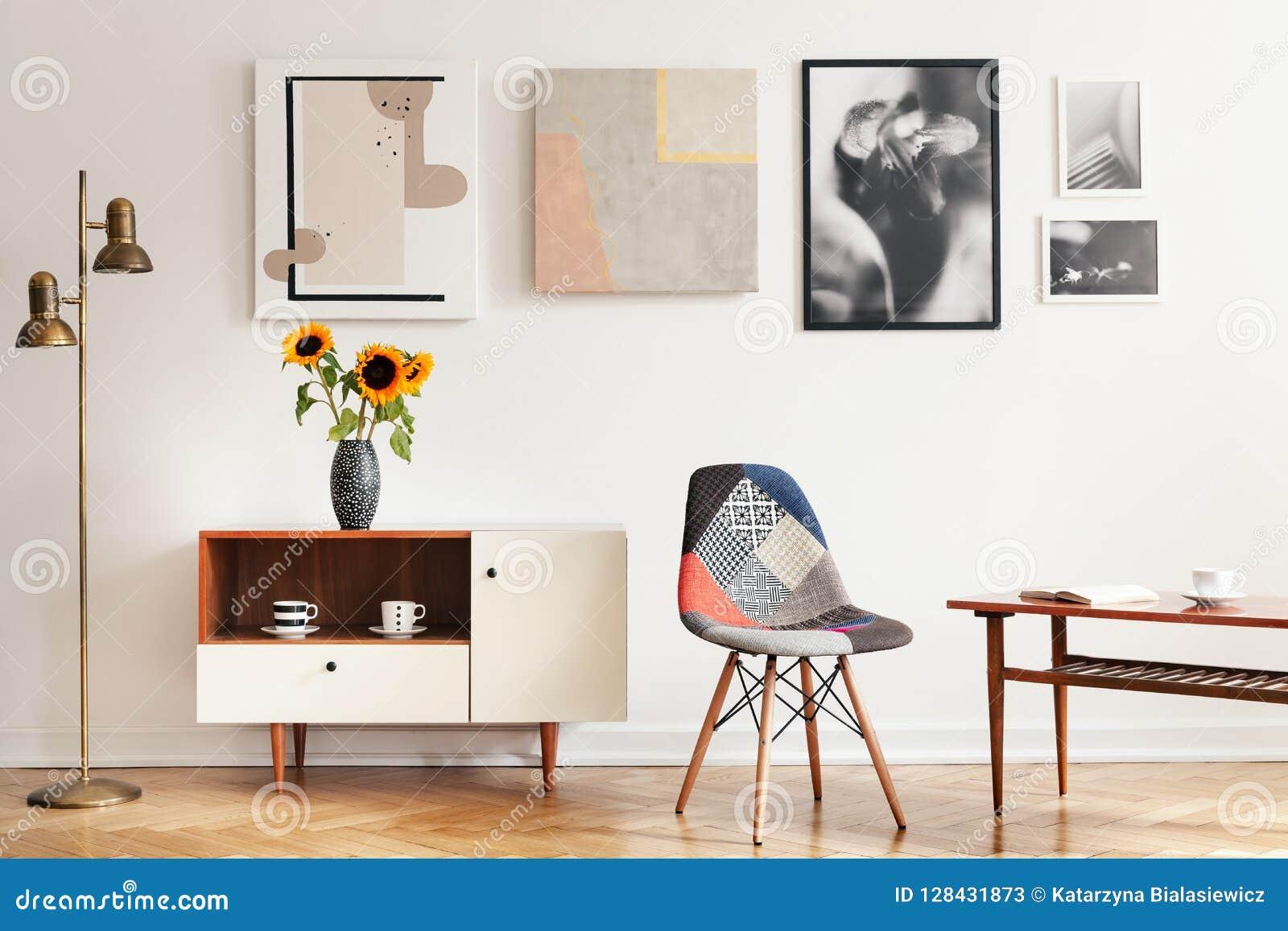 Echte foto van helder eclectisch woonkamerbinnenland met vele affiches, kleurrijke stoel, houten kast met bloemen en koffie tabl