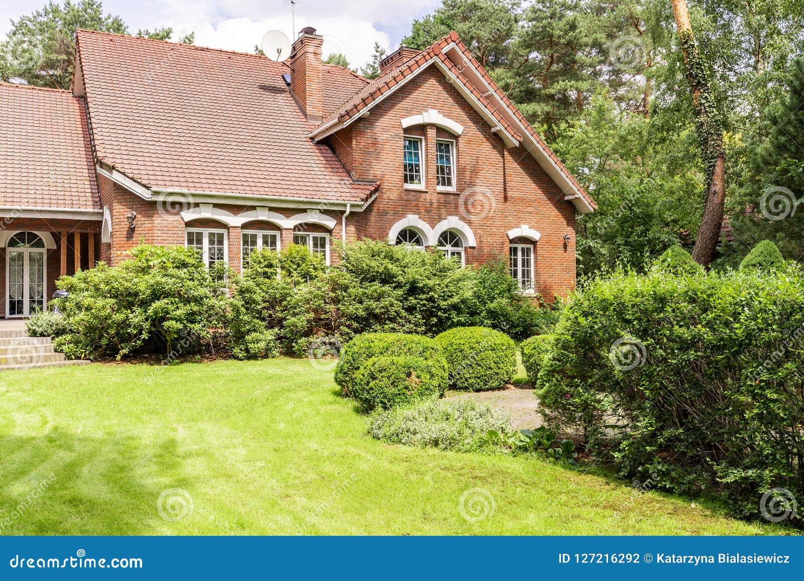 Echte foto van tuin met struiken en mooi baksteenhuis