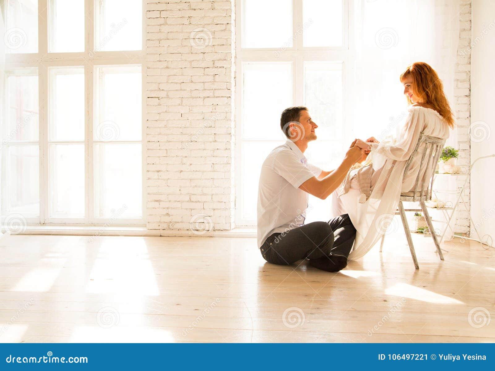 Echtgenootzitting op de vloer, zwangere vrouw op een stoel De echtgenoot bekijkt affectionately zijn vrouw