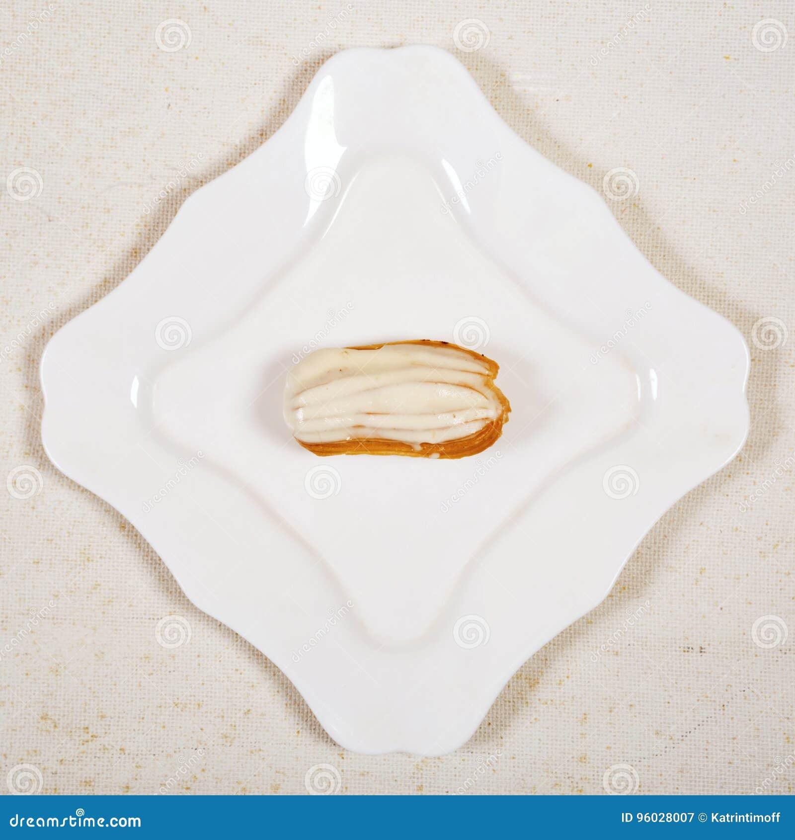 Eclair tort na bielu talerza tle,