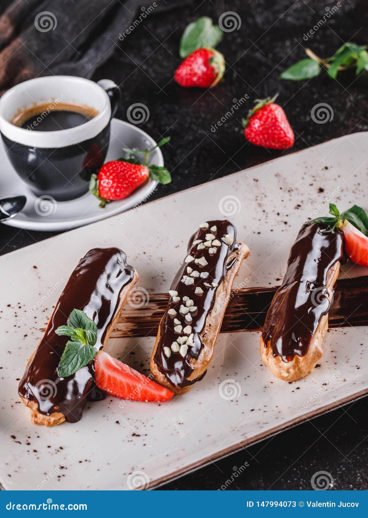 Eclairs caseiros ou profiteroles do bolo com creme, chocolate e morangos no fundo escuro servido com x?cara de caf?