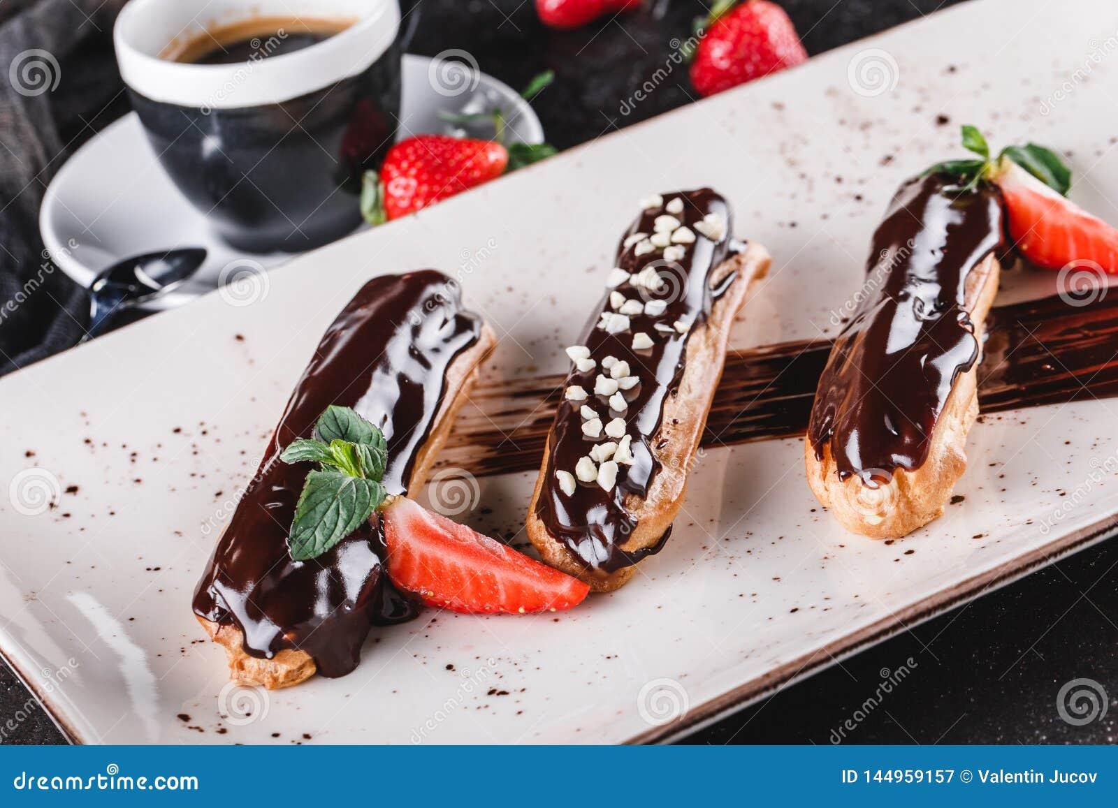 Eclairs caseiros ou profiteroles do bolo com creme, chocolate e morangos no fundo escuro servido com x?cara de caf