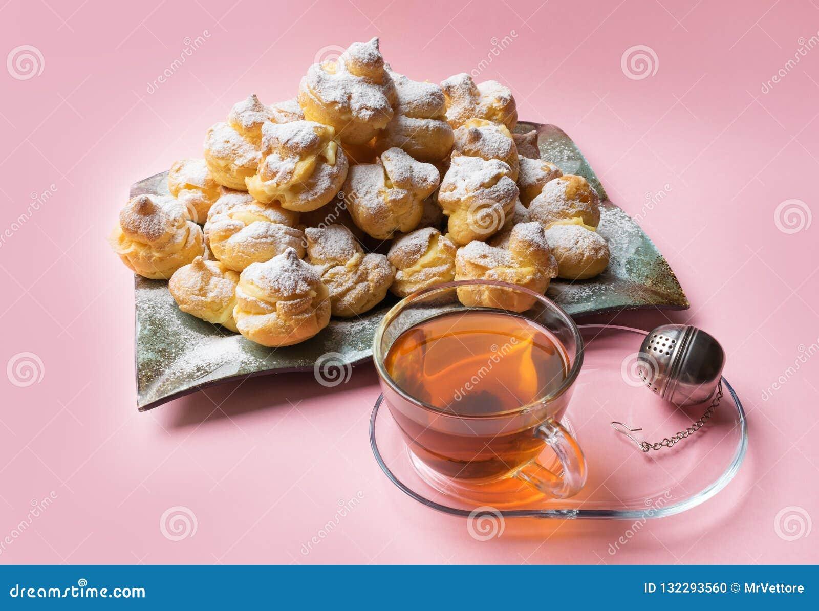 Eclairs deliciosos asperjados con el azúcar de formación de hielo y la taza de té en un fondo rosado Profiteroles hechos en casa
