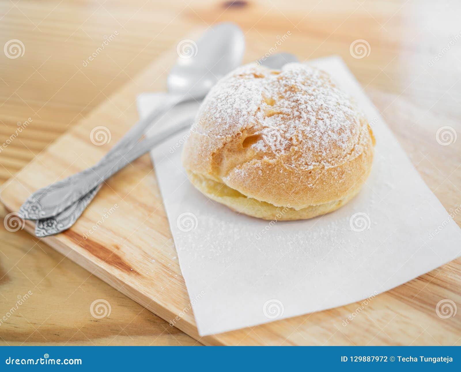 Eclairs deliciosos polvilhados com o açúcar de crosta de gelo