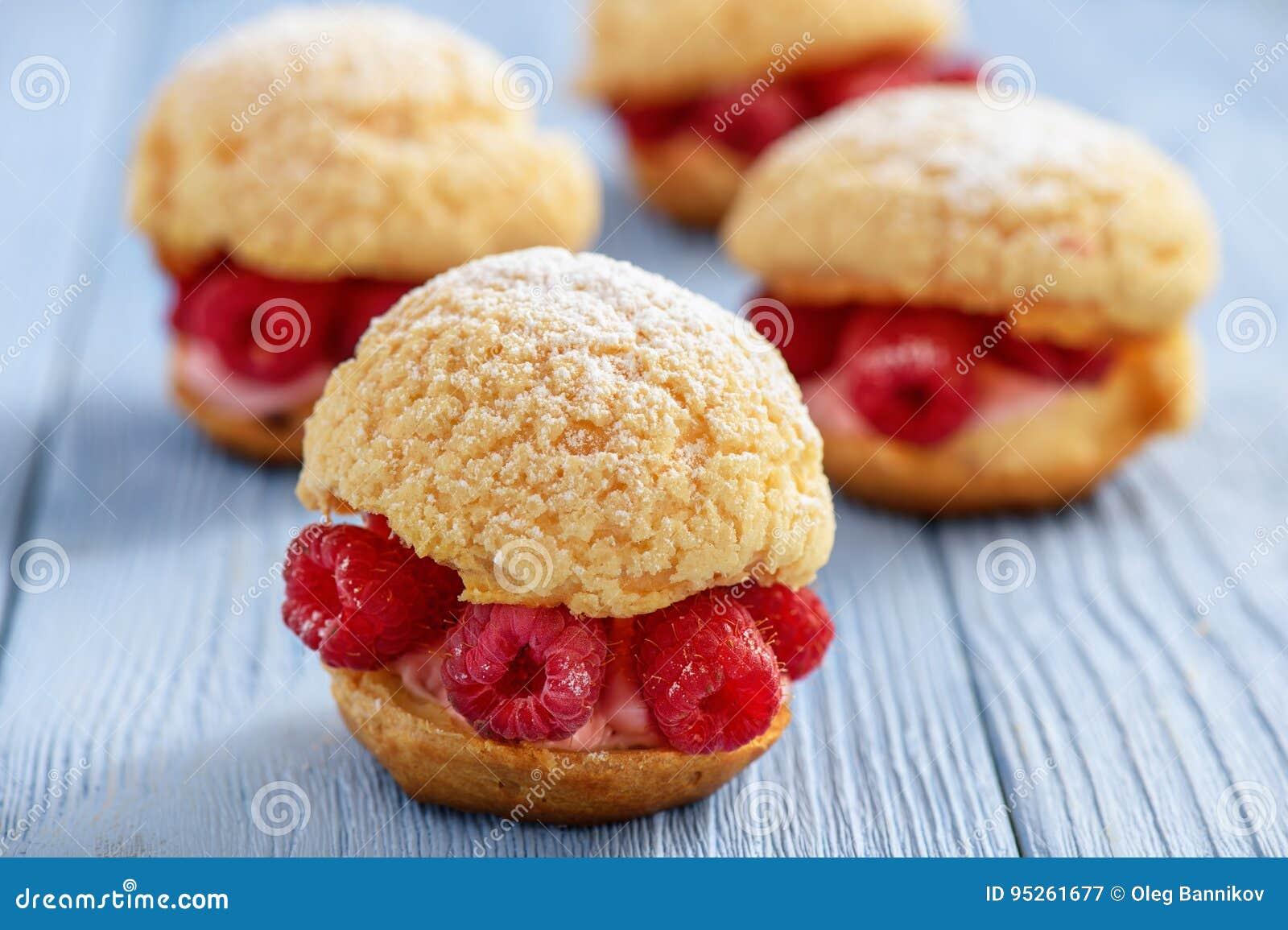 Eclairs with mascarpone cream and raspberries.
