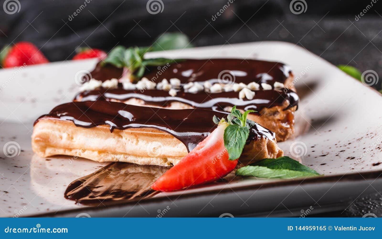 Eclairs o profiteroles hechos en casa de la torta con natillas, chocolate y fresas en el fondo oscuro servido con la taza de caf?