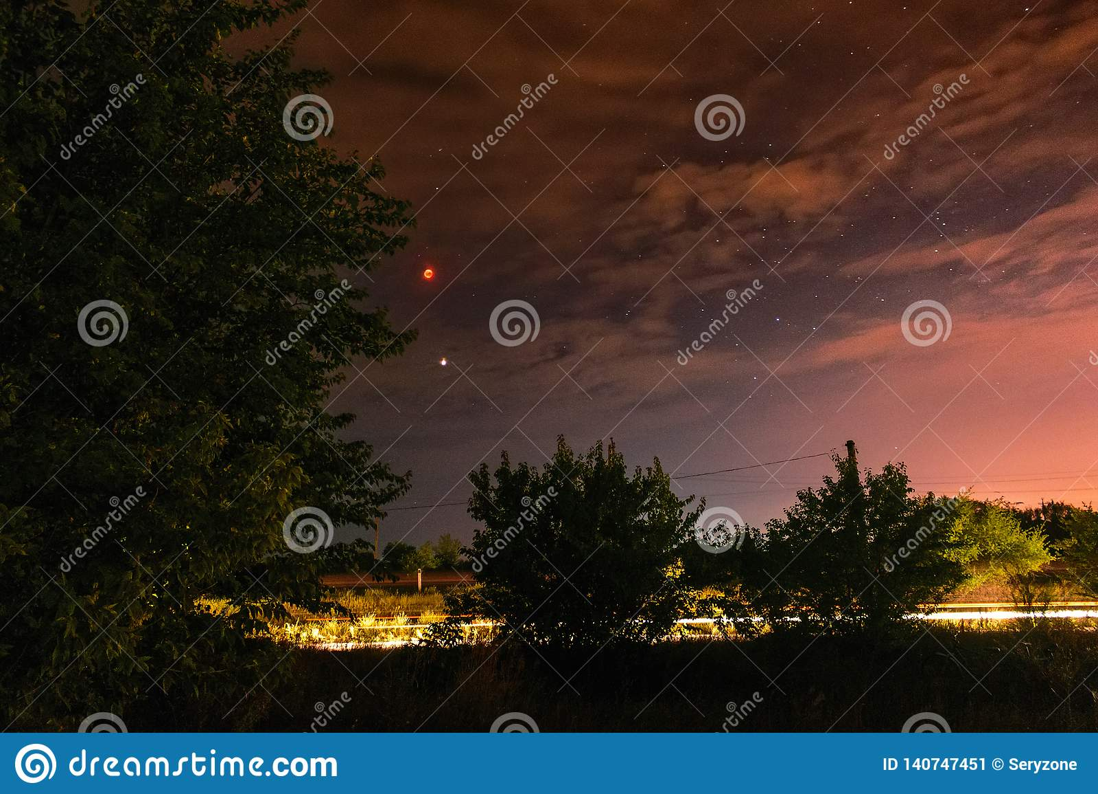 Eclipse de la Luna Llena en el cielo nocturno oscuro nublado