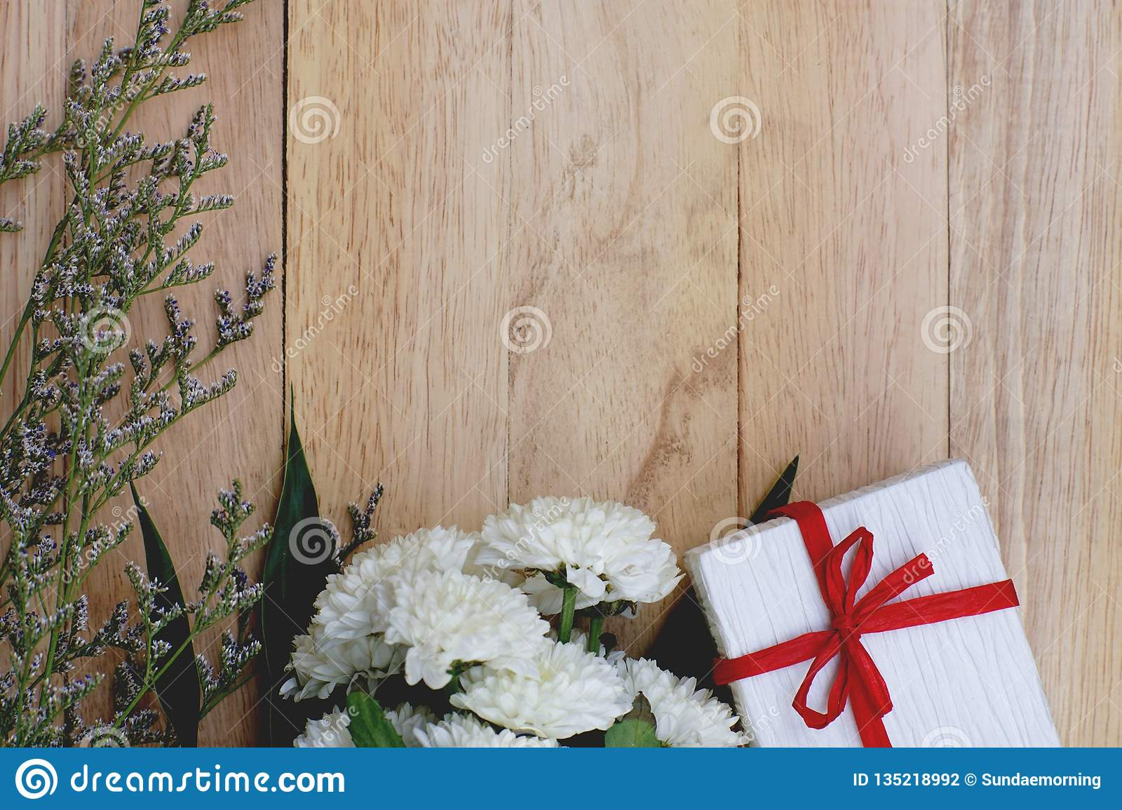 Eco friendly brown paper wrapped gift box present decorated with rose and other flowers on wooden background, valentine ornamental