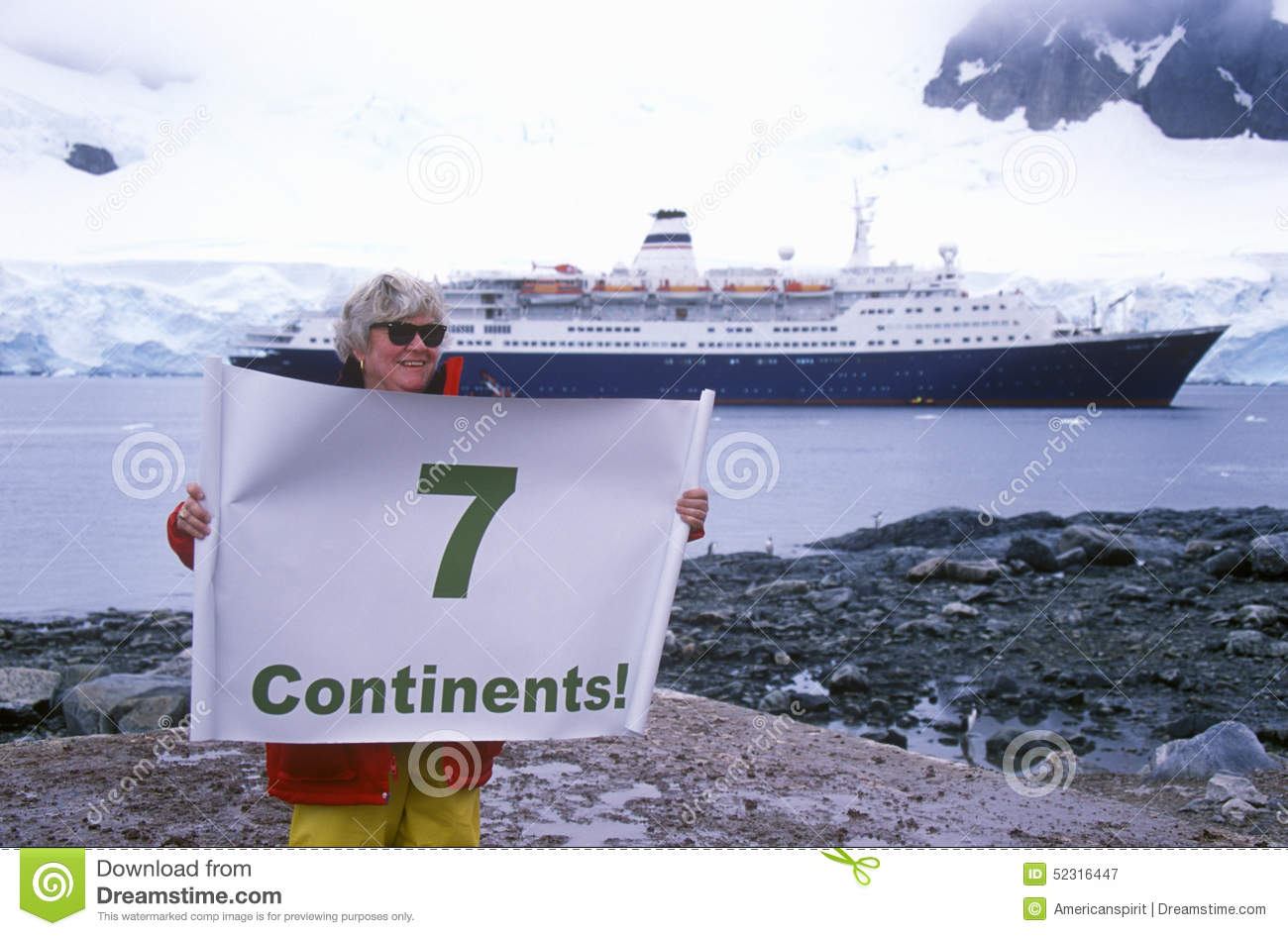 Ecological tourist from cruise ship Marco Polo with Seven Continents sign at Paradise Harbor, Antarctica