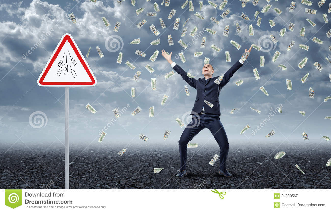 Ecstatic businessman standing under many dollar bills falling from the sky with a traffic warning sign `Money` nearby.