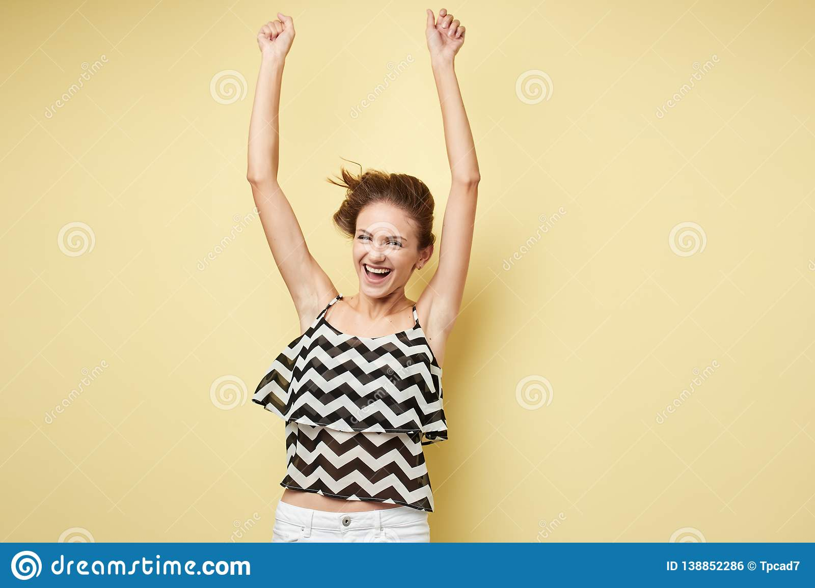 Ecstatic girl dressed in a striped top and white jeans happily shouts on the yellow background in the studio
