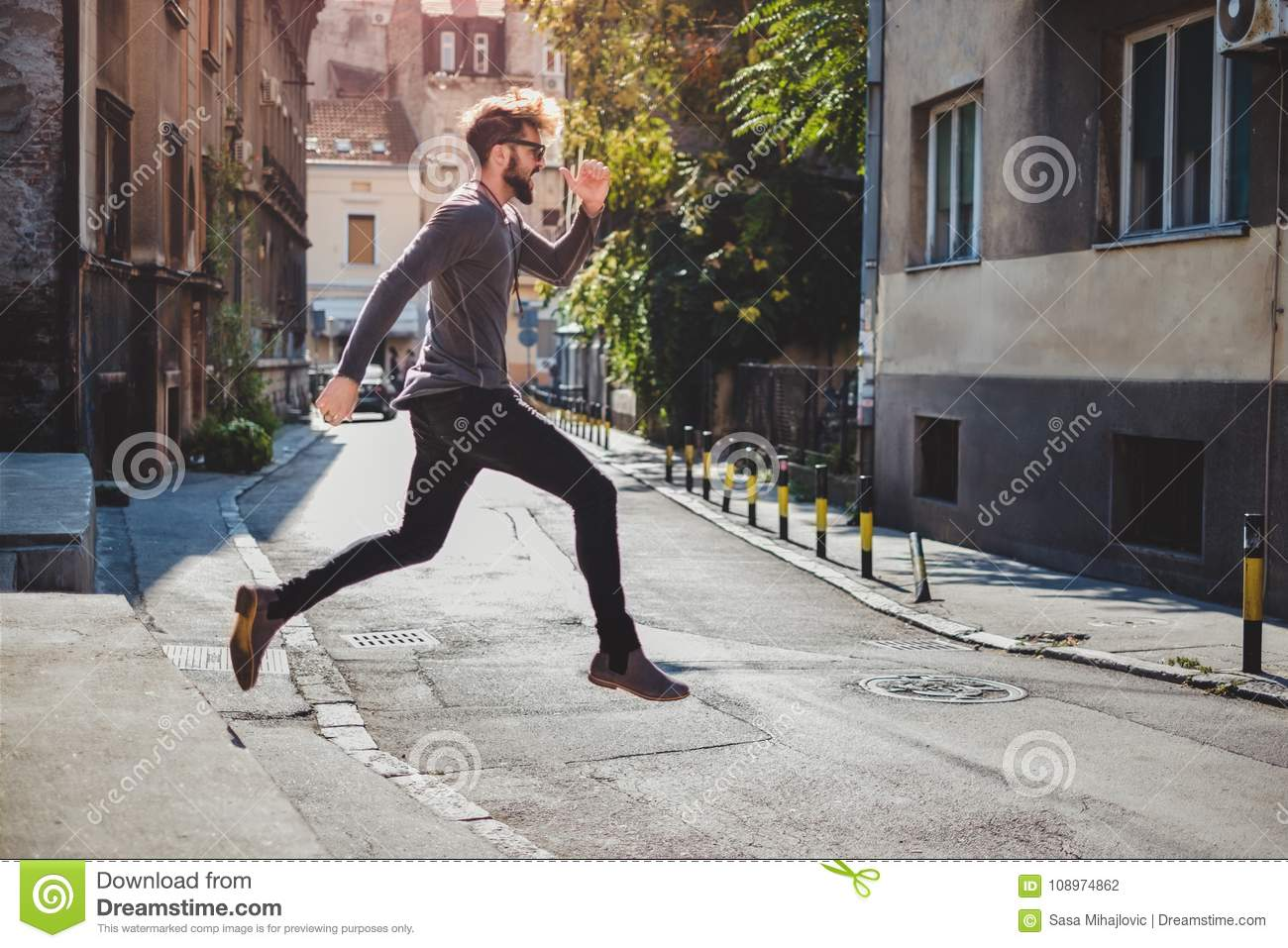 Ecstatic hipster jumps in the street with his mouth open