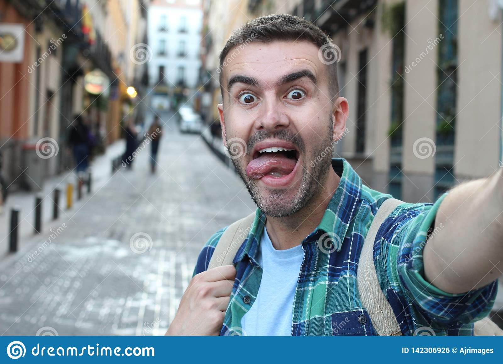 Ecstatic man taking a selfie outdoors