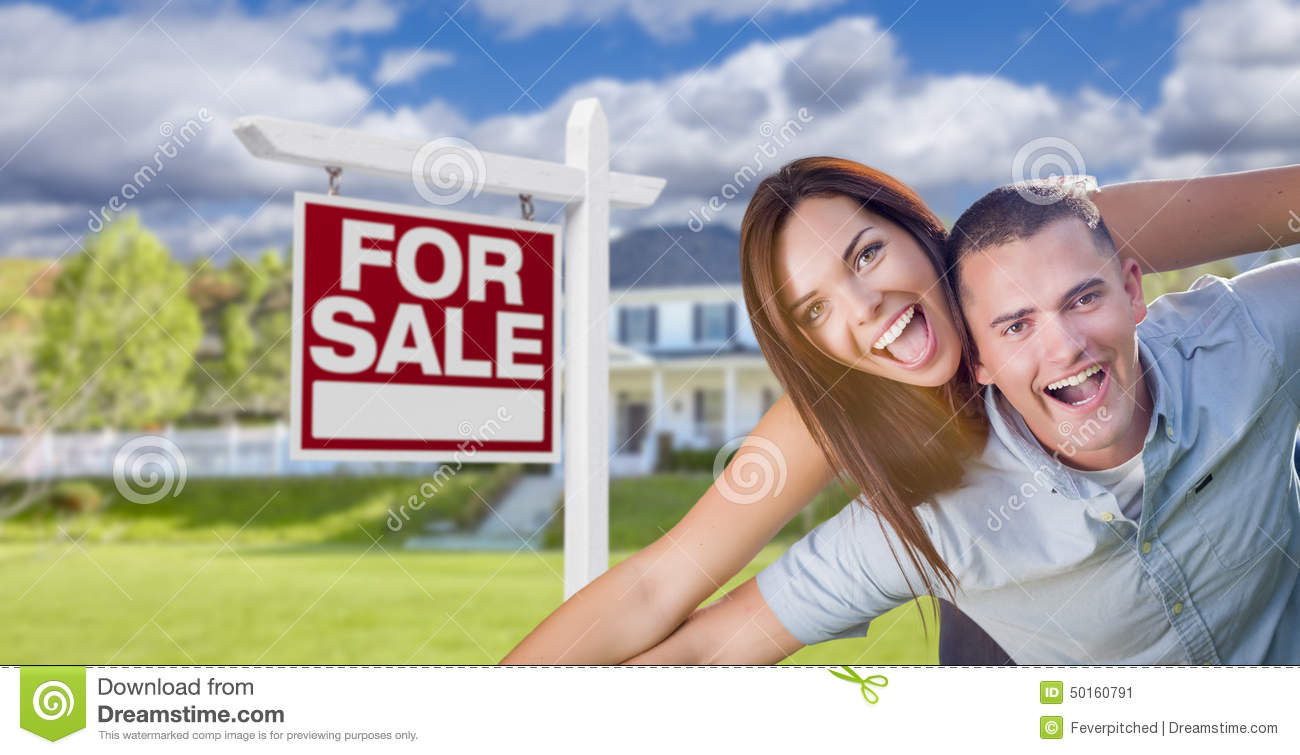 Ecstatic Young Military Couple In Front of Home with For Sale Sign