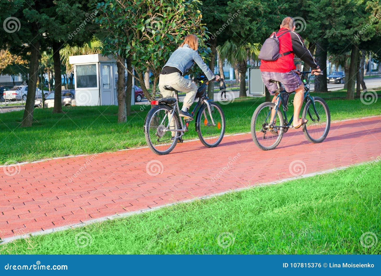 Edad mayor activa y vida urbana - un par de habitantes de ciudad un hombre y una mujer en una edad van en las bicicletas en la tr