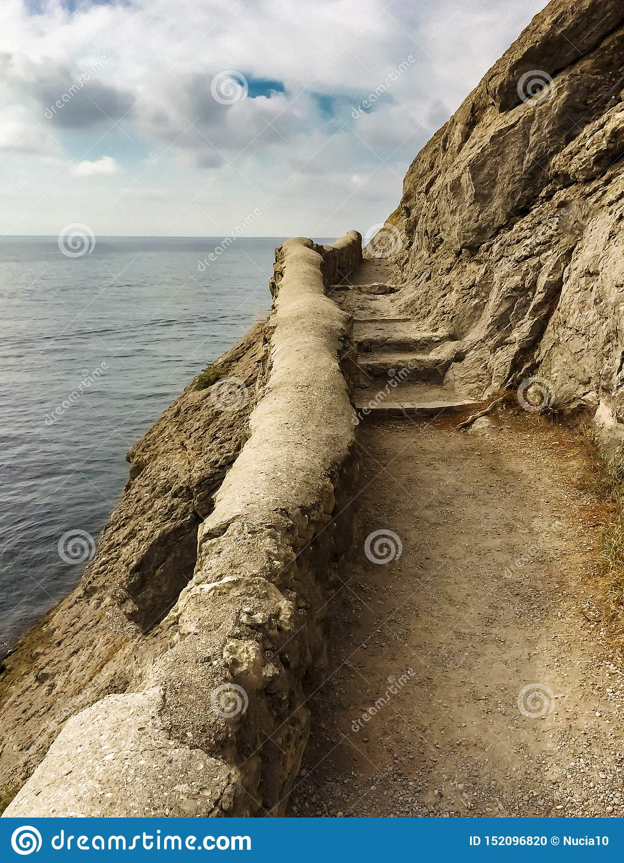 Edge of the cliff with an ancient stone path along the sea with stone steps against the sea and clouds, vertical frame