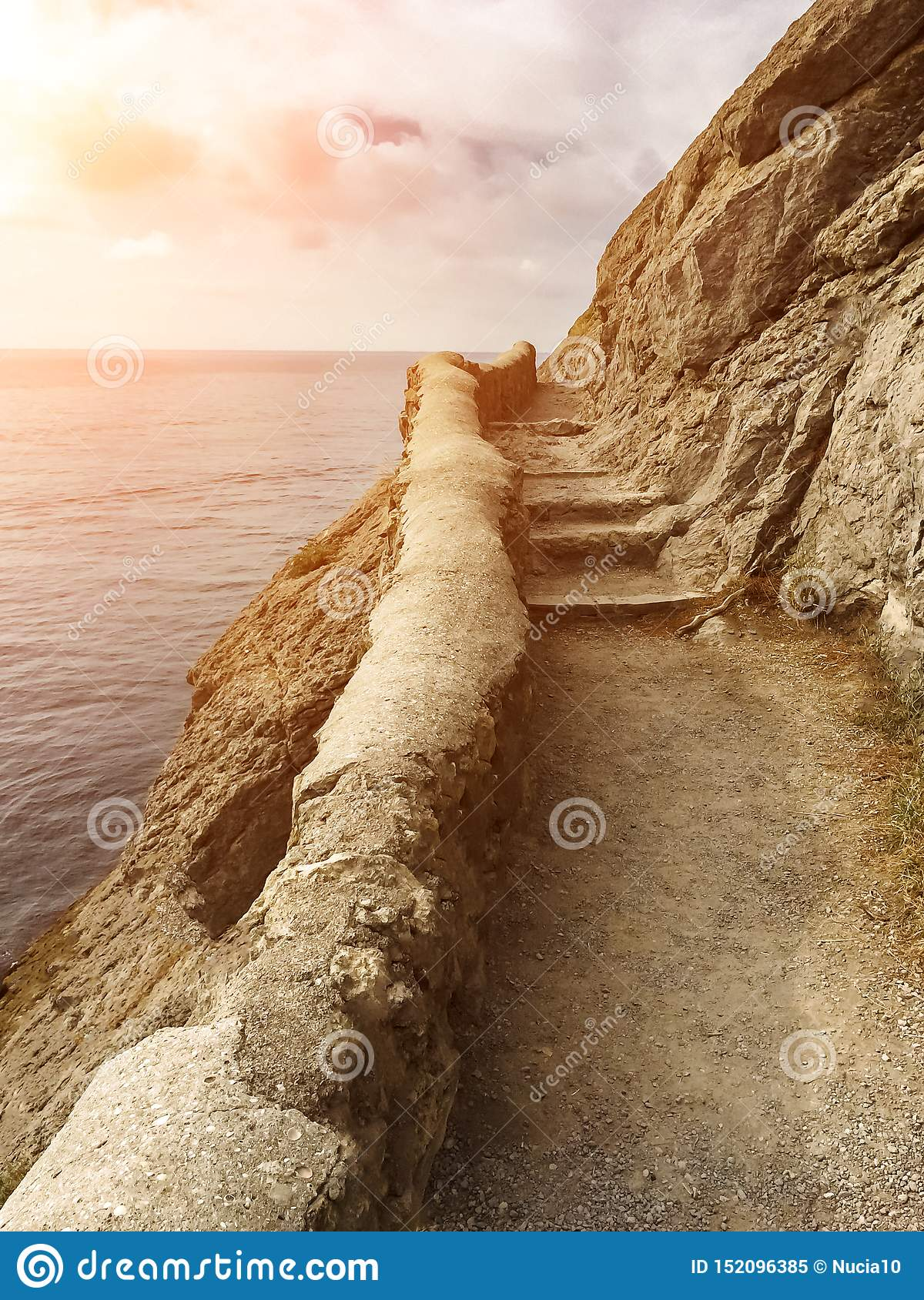 Edge of the cliff with an ancient stone path along the sea with stone steps against the sea with the setting sun, vertical frame