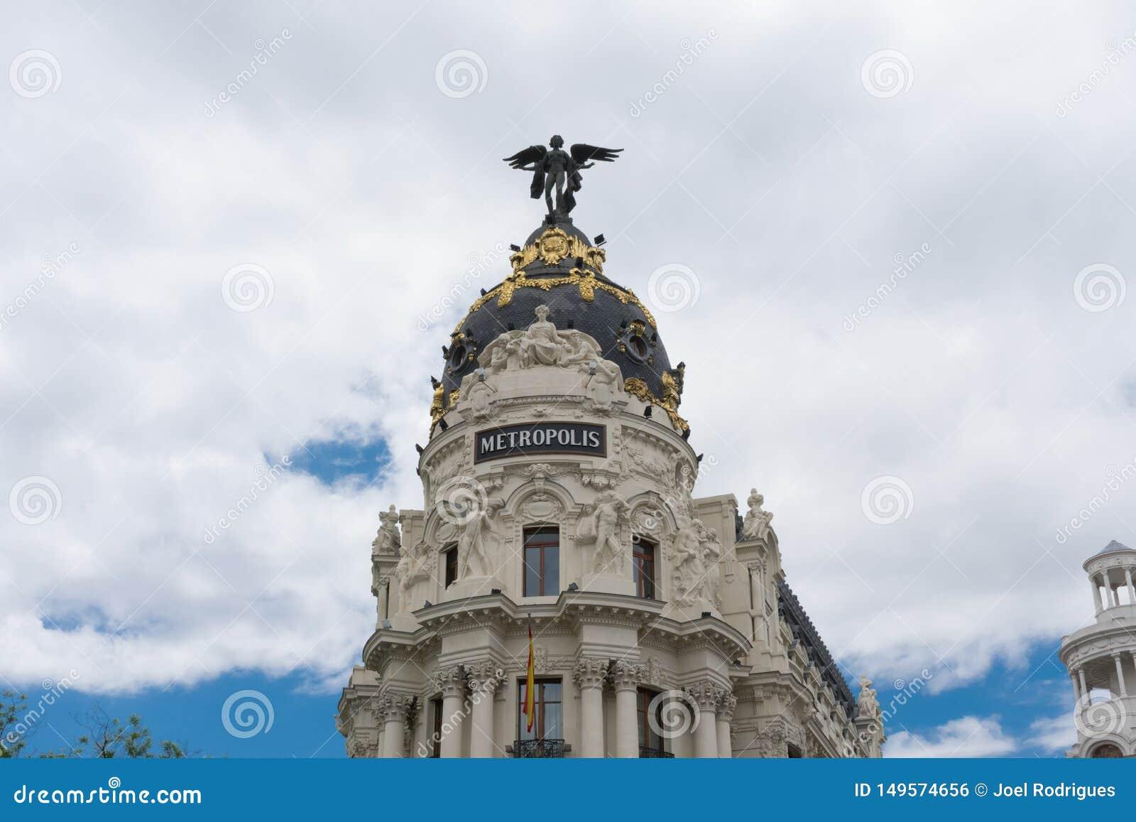 Edificio cubierto con una cúpula con la estatua del ángel, metrópoli en Madrid