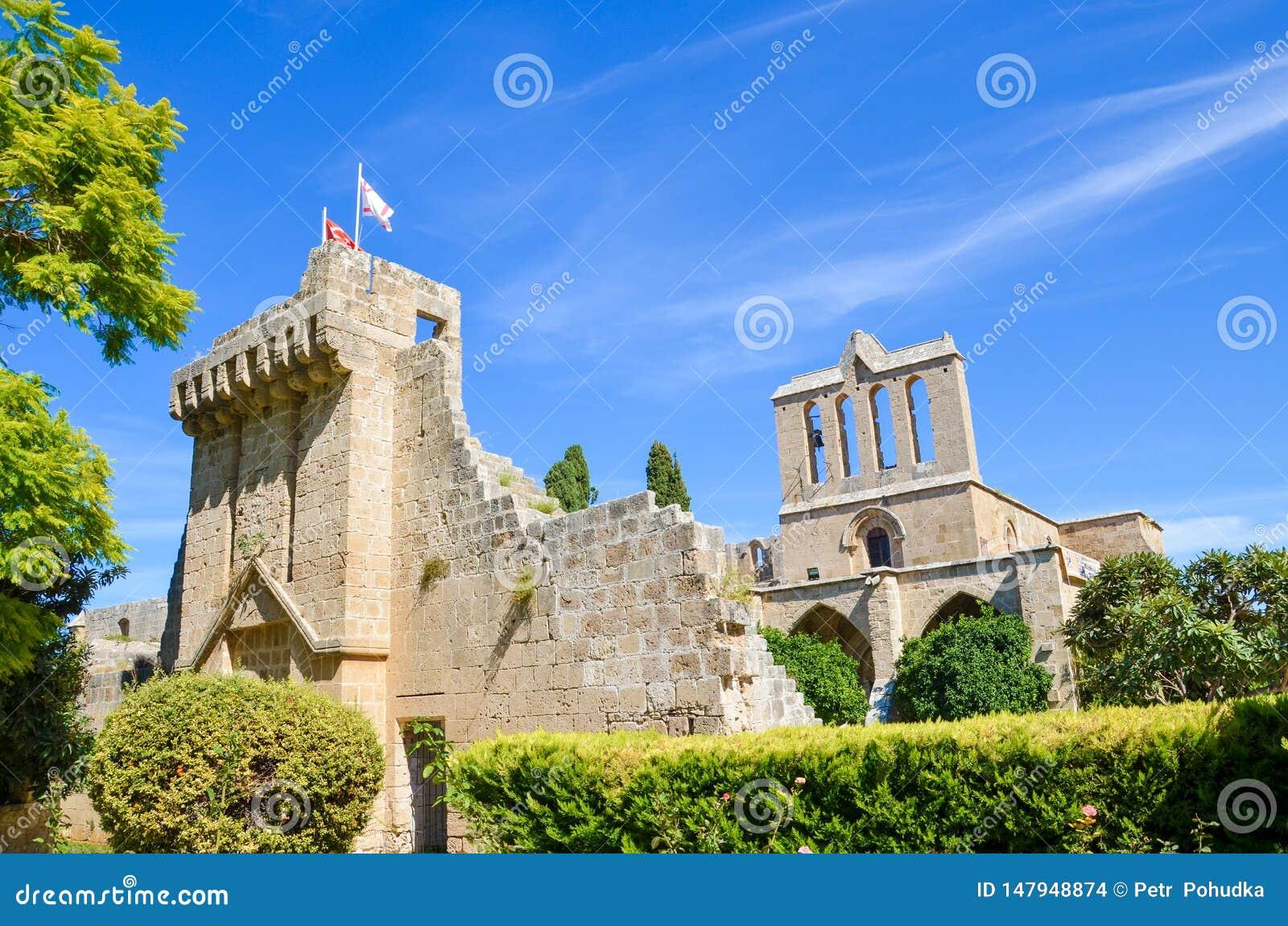 Edificio hermoso de la abadía medieval de Bellapais tomada con el parque adyacente y con el cielo azul Las ruinas del monasterio